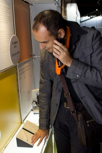 Photograph of a man listening to an audio device while touching a tactile exhibit